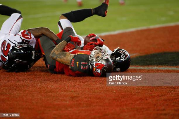 Wide receiver Mike Evans of the Tampa Bay Buccaneers hauls in a 42yard pass from quarterback Jameis Winston while getting pressure from cornerback...