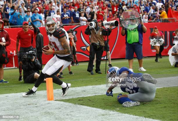 Wide receiver Mike Evans of the Tampa Bay Buccaneers runs through the end zone in front of cornerback Eli Apple of the New York Giants after hauling...