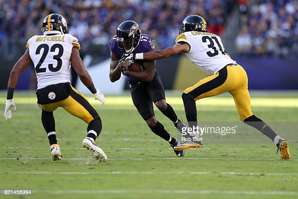 Wide receiver Mike Wallace of the Baltimore Ravens carries the ball against cornerback Ross Cockrell and free safety Mike Mitchell of the Pittsburgh...