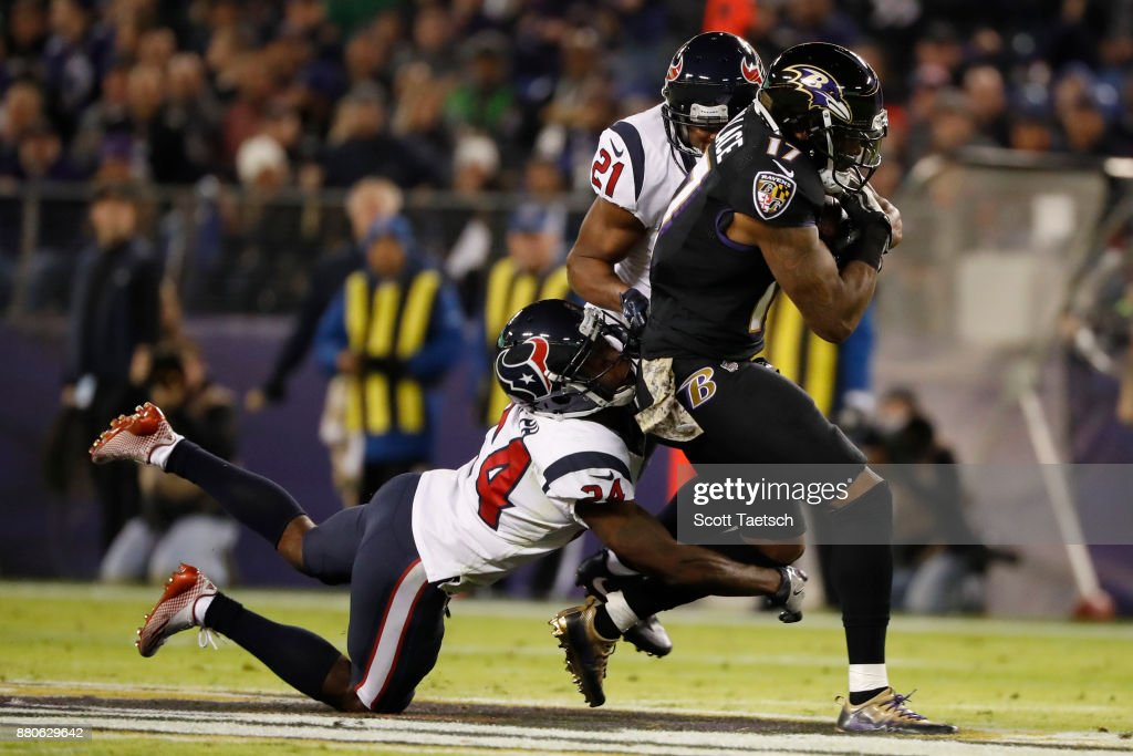 Wide Receiver Mike Wallace #17 of the Baltimore Ravens carries the ball as he is tackled by cornerback Johnathan Joseph #24 of the Houston Texans in the second quarter at M&T Bank Stadium on November 27, 2017 in Baltimore, Maryland.