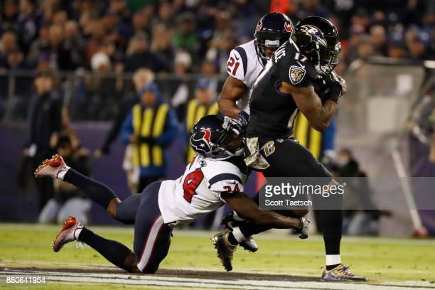 Wide Receiver Mike Wallace of the Baltimore Ravens carries the ball as he is tackled by cornerback Johnathan Joseph of the Houston Texans in the...