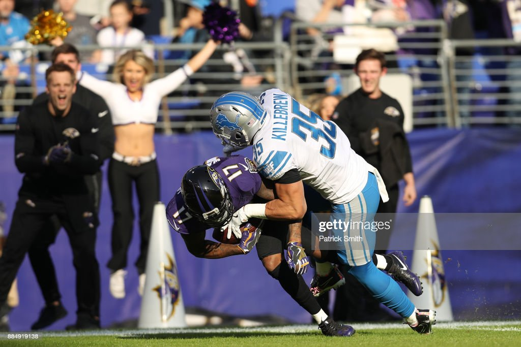 Wide Receiver Mike Wallace #17 of the Baltimore Ravens is tackled by strong safety Miles Killebrew #35 of the Detroit Lions in the second quarter at M&T Bank Stadium on December 3, 2017 in Baltimore, Maryland.