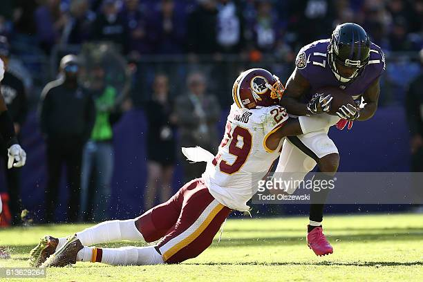 Wide receiver Mike Wallace of the Baltimore Ravens runs with the ball while being tackled by strong safety Duke Ihenacho of the Washington Redskins...