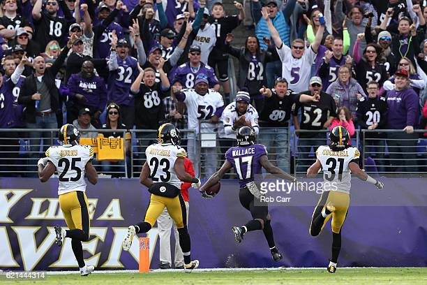 Wide receiver Mike Wallace of the Baltimore Ravens scores a first quarter touchdown past free safety Mike Mitchell and cornerback Ross Cockrell of...