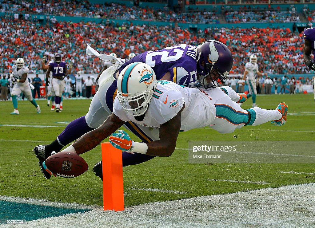 Wide receiver Mike Wallace #11 of the Miami Dolphins scores a third quarter touchdown as free safety Harrison Smith #22 of the Minnesota Vikings defends during a game at Sun Life Stadium on December 21, 2014 in Miami Gardens, Florida.