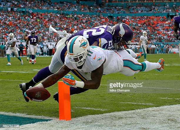 Wide receiver Mike Wallace of the Miami Dolphins scores a third quarter touchdown as free safety Harrison Smith of the Minnesota Vikings defends...