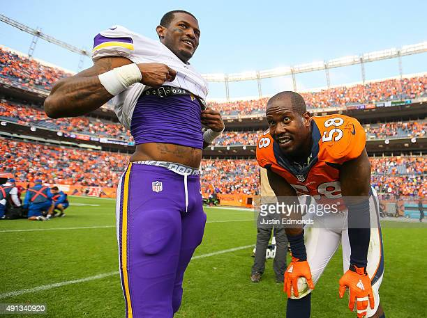 Wide receiver Mike Wallace of the Minnesota Vikings and outside linebacker Von Miller of the Denver Broncos meet at midfield before exchanging...
