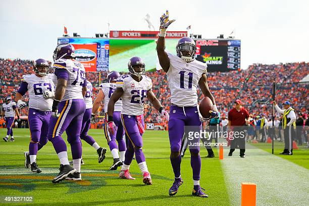 Wide receiver Mike Wallace of the Minnesota Vikings celebrates after catching a pass for a second quarter touchdown against the Denver Broncos during...