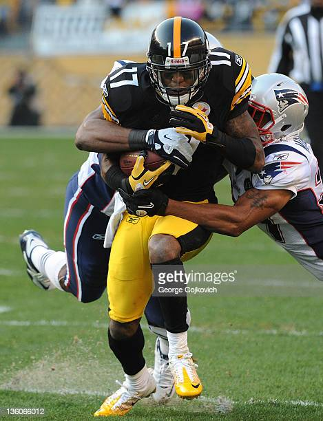 Wide receiver Mike Wallace of the Pittsburgh Steelers is tackled by linebacker Jerod Mayo and cornerback Antwaun Molden of the New England Patriots...