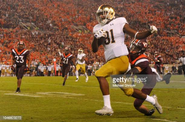 Wide receiver Miles Boykin of the Notre Dame Fighting Irish evades the tackle from defensive back Caleb Farley of the Virginia Tech Hokies and scores...