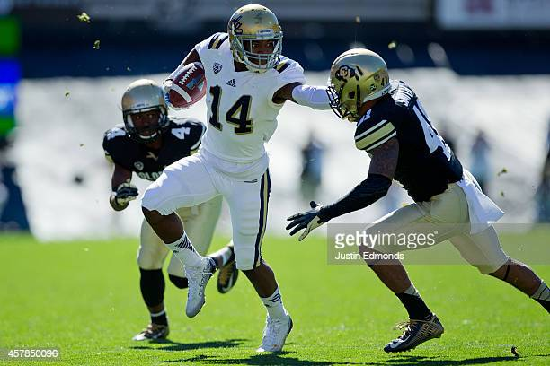 Wide receiver Mossi Johnson of the UCLA Bruins stiffarms defensive back Terrel Smith of the Colorado Buffaloes after making a catch during the first...