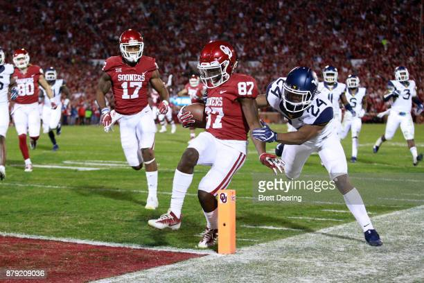 Wide receiver Myles Tease of the Oklahoma Sooners scores as cornerback Hakeem Bailey of the West Virginia Mountaineers defends at Gaylord Family...