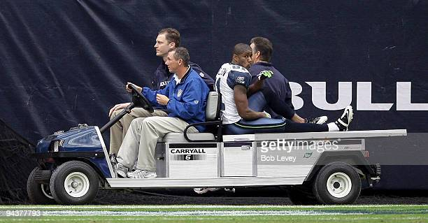 Wide receiver Nate Burleson of the Seattle Seahawks is carted off the field in the third quarter against the Houston Texans at Reliant Stadium on...