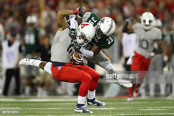 Wide receiver Nate Phillips of the Arizona Wildcats is tackled by defensive back Trayvon Henderson of the Hawaii Warriors after a reception during...