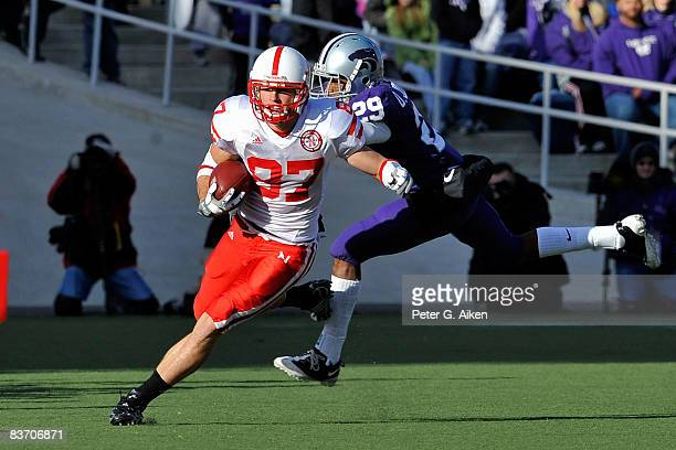 Wide receiver Nate Swift of the Nebraska Cornhuskers rushes up field after making a catch past defensive back Otis Johnson of the Kansas State...