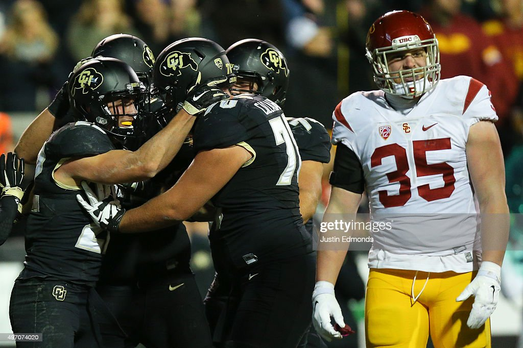 Wide receiver Nelson Spruce #22 of the Colorado Buffaloes celebrates his second quarter touchdown with offensive lineman Shane Callahan #70 as linebacker Cameron Smith #35 of the USC Trojans walks away at Folsom Field on November 13, 2015 in Boulder, Colorado.