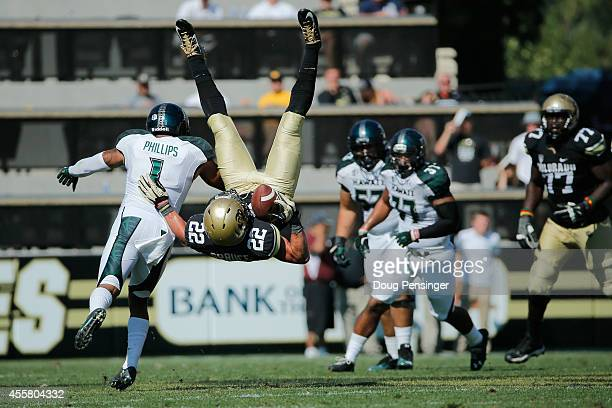 Wide receiver Nelson Spruce of the Colorado Buffaloes makes a pass reception and is upended by defensive back Ne'Quan Phillips of the Hawaii Rainbow...