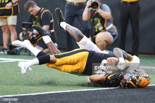 Wide receiver Nico Ragaini of the Iowa Hawkeyes is brought down short of a touchdown during the second half by linebacker Marvin Pierre of the Kent...