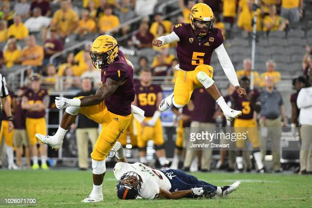 Wide receiver N'Keal Harry and quarterback Manny Wilkins of the Arizona State Sun Devils jump over cornerback Clayton Johnson of the UTSA Roadrunners...