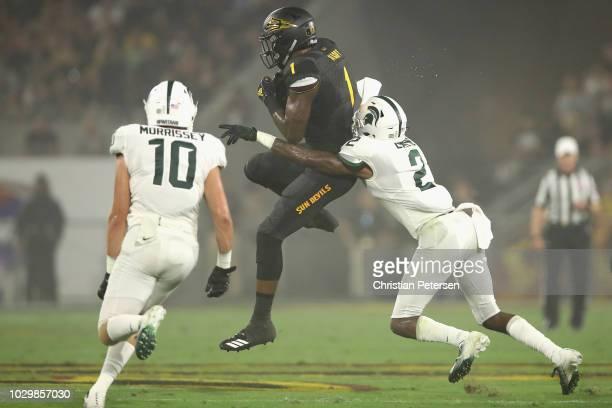Wide receiver N'Keal Harry of the Arizona State Sun Devils mkaes a leaping catch over cornerback Justin Layne of the Michigan State Spartans during...