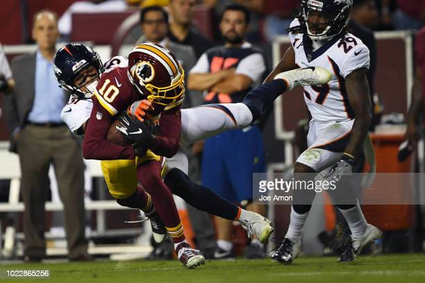 Wide receiver Paul Richardson of the Washington Redskins makes a catch in front of defensive back Justin Simmons of the Denver Broncos at FedExField...