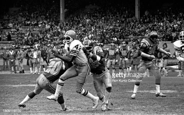 Wide receiver Paul Warfield of the Cleveland Browns is hit by cornerbacks Mike Williams and Tom Hayes of the San Diego Chargers during a game at...