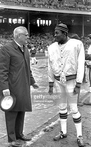 Wide receiver Paul Warfield of the Cleveland Browns talks with head coach Woody Hayes of the Ohio State Buckeyes during a game on circa 1966 at...