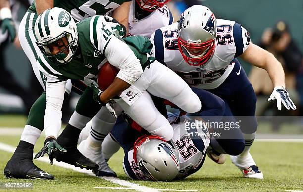 Wide receiver Percy Harvin of the New York Jets is tackled by middle linebacker Akeem Ayers of the New England Patriots during a game at MetLife...