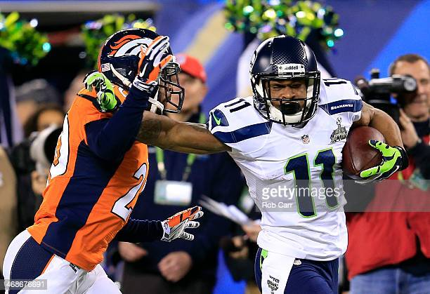 Wide receiver Percy Harvin of the Seattle Seahawks tries to avoid the tackle of strong safety Duke Ihenacho of the Denver Broncos during Super Bowl...