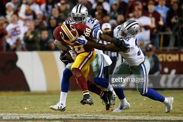 Wide receiver Pierre Garcon of the Washington Redskins carries the ball against free safety Byron Jones and cornerback Brandon Carr of the Dallas...