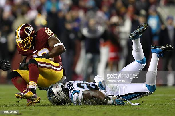 Wide receiver Pierre Garcon of the Washington Redskins carries the ball against cornerback James Bradberry of the Carolina Panthers in the second...