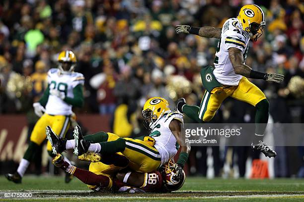 Wide receiver Pierre Garcon of the Washington Redskins is tackled by cornerback LaDarius Gunter and strong safety Morgan Burnett of the Green Bay...