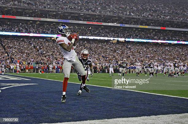 Wide receiver Plaxico Burress of the New York Giants catches a 13-yard touchdown pass in the fourth quarter over Ellis Hobbs of the New England...