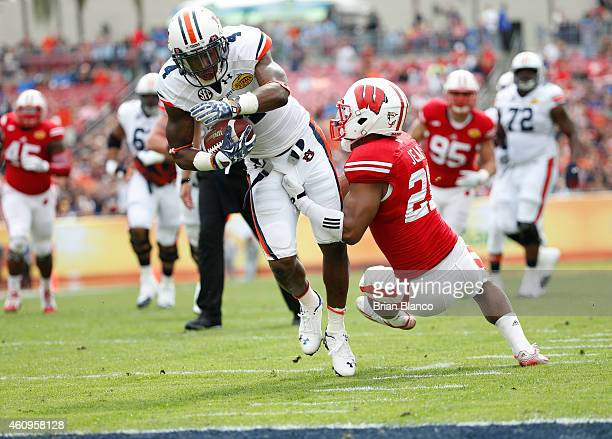 Wide receiver Quan Bray of the Auburn Tigers is stopped by cornerback Peniel Jean of the Wisconsin Badgers to bring up first and goal during the...