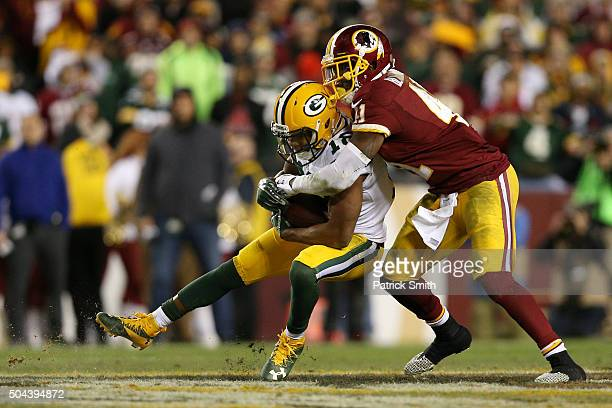 Wide receiver Randall Cobb of the Green Bay Packers carries the ball against cornerback Will Blackmon of the Washington Redskins in the fourth...