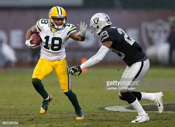 Wide Receiver Randall Cobb of the Green Bay Packers looks to evade Corner Back David Amerson of the Oakland Raiders at Oco Coliseum on December 20...