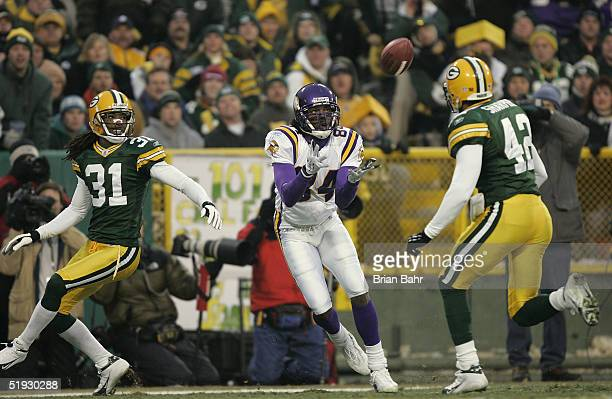 Wide receiver Randy Moss of the Minnesota Vikings catches a touchdown pass in between the defense of cornerback Al Harris and safety Darren Sharper...