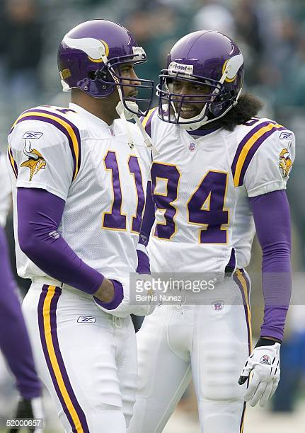 Wide receiver Randy Moss of the Minnesota Vikings smiles as he talks with teammate quarterback Daunte Culpepper prior to the action against the...