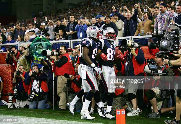 Wide receiver Randy Moss of the New England Patriots is congratulated by teammate Benjamin Watson after catching a sixyard touchdown pass from Tom...