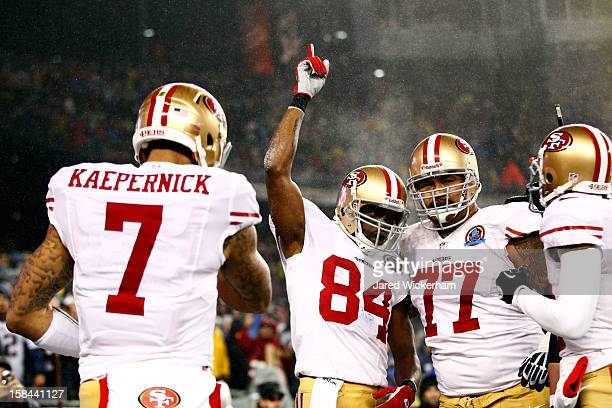 Wide receiver Randy Moss of the San Francisco 49ers celebrates after scoring a touchdown with quarterback Colin Kaepernick and guard Mike Iupati in...