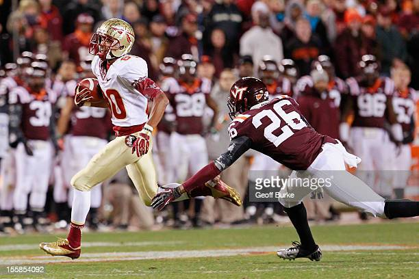 Wide receiver Rashad Greene of the Florida State Seminoles runs with the ball past safety Desmond Frye of the Virginia Tech Hokies to score the...