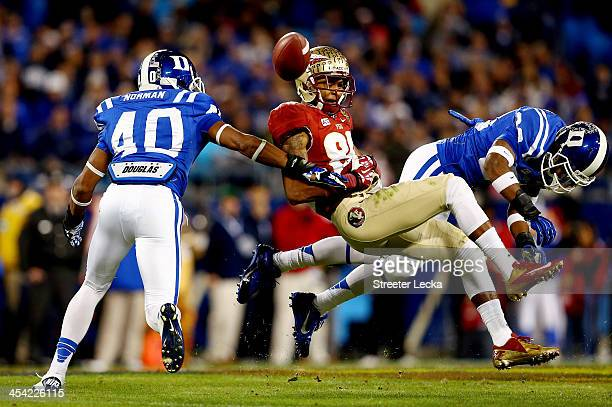 Wide receiver Rashad Greene of the Florida State Seminoles tries to make a catch as cornerback Deondre Singleton and safety Dwayne Norman of the Duke...