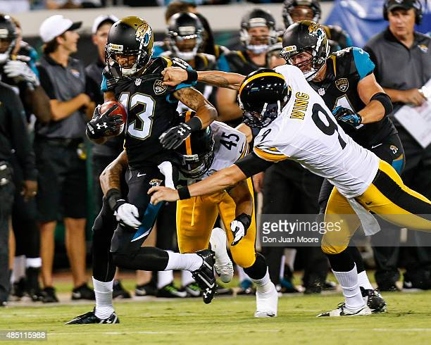Wide Receiver Rashad Greene of the Jacksonville Jaguars is tackled by Fullback Roosevelt Nix and Punter Brad Wing of the Pittsburgh Steelers during a...