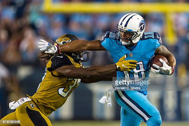 Wide receiver Rashad Greene of the Tennessee Titans carries the ball as Johnathan Cyprien of the Jacksonville Jaguars tries to tackle him during a...