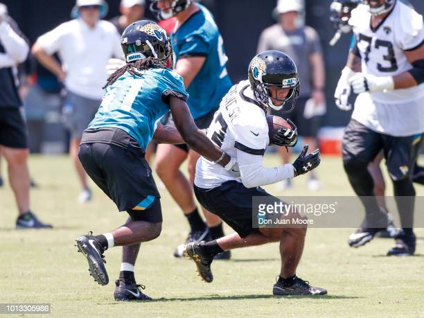 Wide Receiver Rashad Greene Sr #13 makes a catch over Cornerback Tre Herndon of the Jacksonville Jaguars during Training Camp at Dream Finders Homes...