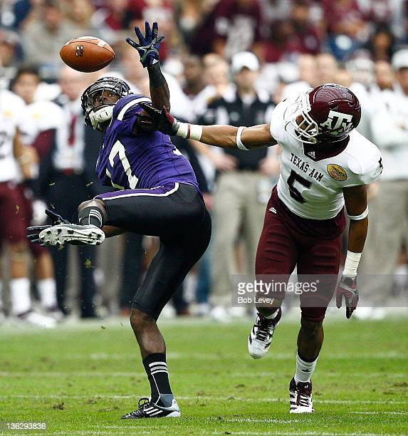Wide receiver Rashad Lawrence of Northwestern Wildcats maintains concentration after defensive back Coryell Judie of Texas AM Aggies tipped the ball...