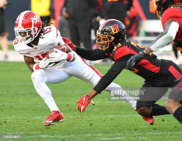 Wide receiver Rashad Ross of the DC Defenders is stopped by cornerback Springs Arrion of the LA Wildcats after a complete pass in the XFL game...