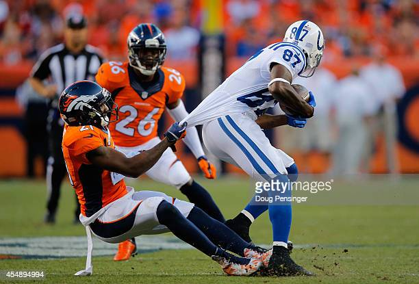 Wide receiver Reggie Wayne of the Indianapolis Colts makes a pass reception and is tackled by cornerback Aqib Talib of the Denver Broncos at Sports...