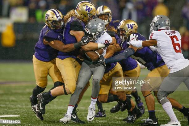 Wide receiver Renard Bell of the Washington State Cougars is tackled by linebacker Ben BurrKirven of the Washington Huskies at Husky Stadium on...
