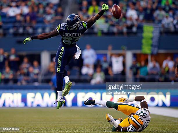 Wide receiver Ricardo Lockette of the Seattle Seahawks goes up in attempt to catch a pass as cornerback Sam Shields of the Green Bay Packers falls to...